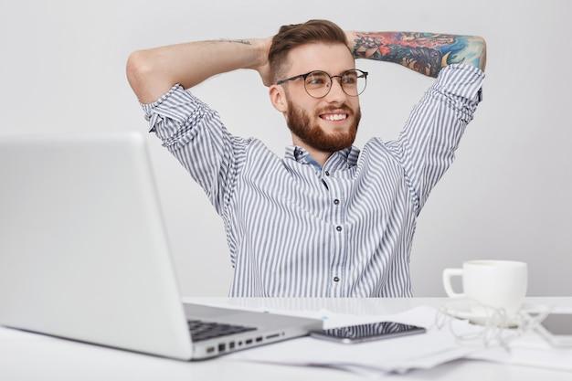 Entspannter geschäftsmann trinkt kaffee, hält hände hinter dem kopf, schaut in die ferne