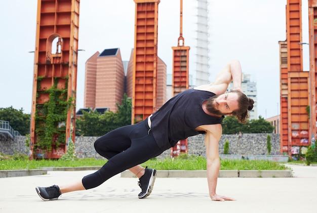 Entspannter gutaussehender mann, der yogaübung tut