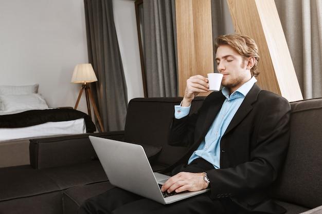 Entspannter hübscher geschäftsmann mit sylischer frisur und bart, der im hotelzimmer sitzt, kaffee trinkt und an neuem startup-projekt arbeitet. bequemer arbeitsplatz