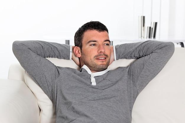 Entspannter hübscher mann, der zu hause auf sofa sitzt