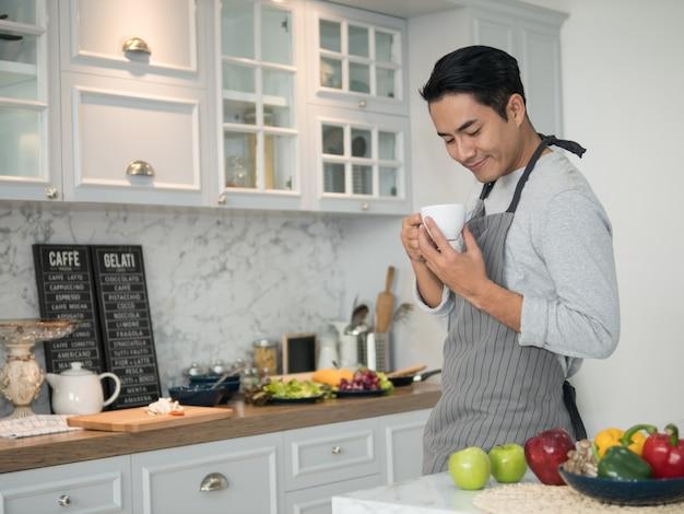 Entspannter junger hübscher asiatischer mann, der zu hause kaffee in der küche trinkt.