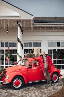 Entspannter junger mann, der einen gred mantel trägt, der sich auf ein verziertes rotes altes auto nahe einem privathaus stützt