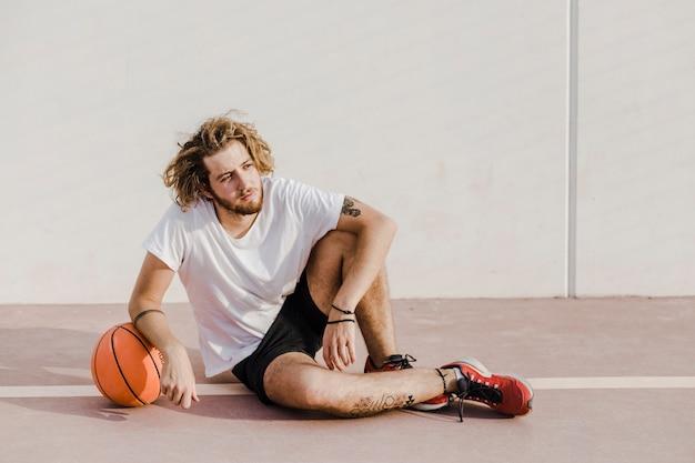 Entspannter junger mann, der vor gericht mit basketball sitzt