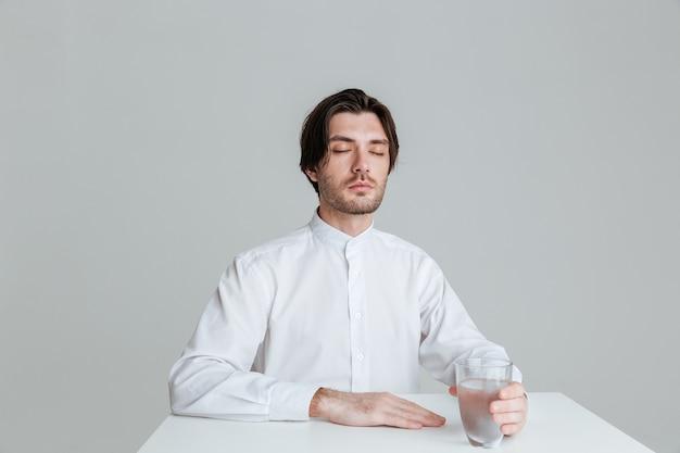 Entspannter junger mann, der wasserglas hält, während er am tisch sitzt, isoliert an der grauen wand