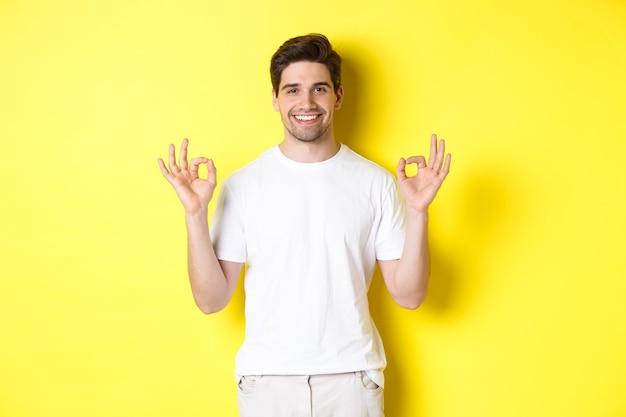 Entspannter kerl lächelt, zeigt gute zeichen, billigt oder stimmt zu, steht vor gelbem hintergrund.