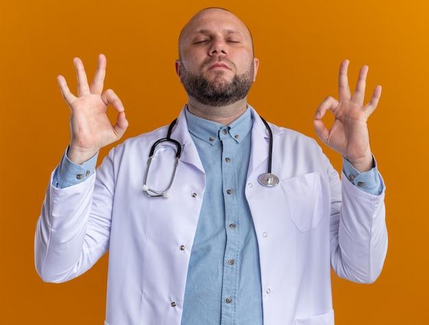 Entspannter männlicher arzt mittleren alters, der ein medizinisches gewand und ein stethoskop trägt und mit geschlossenen augen meditiert