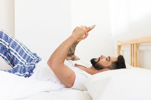 Entspannter mann, der auf bett unter verwendung des mobiltelefons liegt