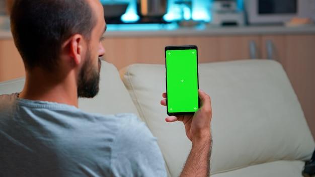 Entspannter mann, der smartphone mit mock-up-chroma-key-display mit grünem bildschirm anschaut, während er sich auf dem sofa entspannt. kaukasische männliche holding im horizontalen modus telefon mit isoliertem display spät in der nacht in der küche