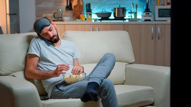 Entspannter mann, der über internetverbindung auf dem smartphone spricht. kaukasischer mann sitzt auf der couch und schaut sich unterhaltungsfilme an, während er spät in der nacht popcorn in der küche isst