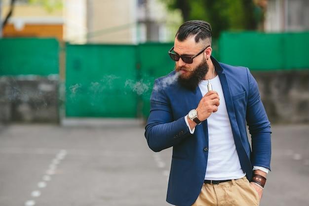 Entspannter mann, eine elektronische zigarre rauchen