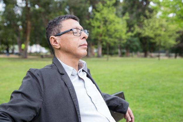 Entspannter mann von mittlerem alter, der auf bank im park sitzt