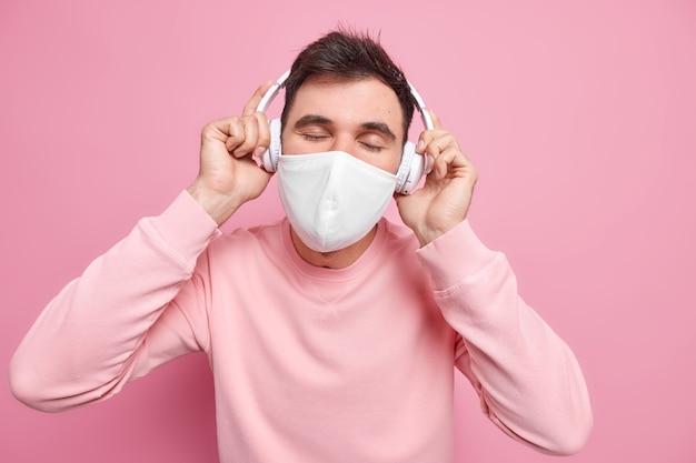 Entspannter, mit coronavirus infizierter mann bleibt allein zu hause bei selbstisolation hält die augen geschlossen trägt eine schützende gesichtsmaske genießt lieblingsmusik verwendet drahtlose kopfhörer in einem lässigen pullover sweat