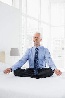 Entspannter reifer geschäftsmann, der in der lotoslage auf bett sitzt