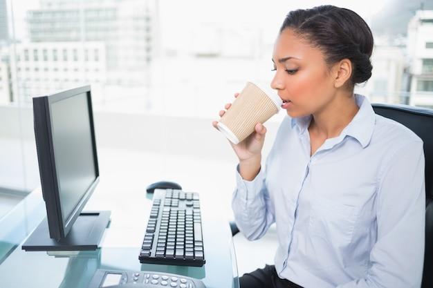 Entspannter trinkender kaffee der jungen dunkelhaarigen geschäftsfrau