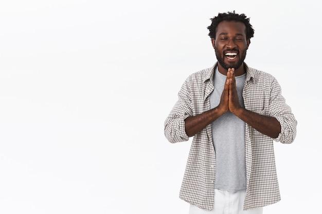 Entspannter und friedlicher fröhlicher afroamerikanischer bärtiger mann mit afro-frisur
