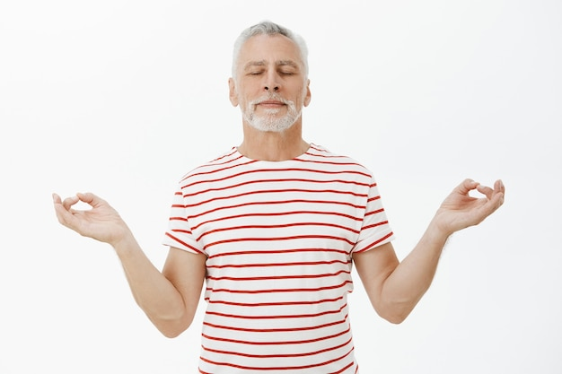Entspannter und geduldiger älterer bärtiger mann, der meditiert, praktiziert yoga