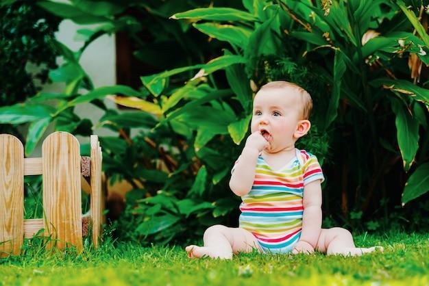 Entspanntes baby, das das gefühl hat, die frische des grases auf seinen bloßen füßen zu bemerken.