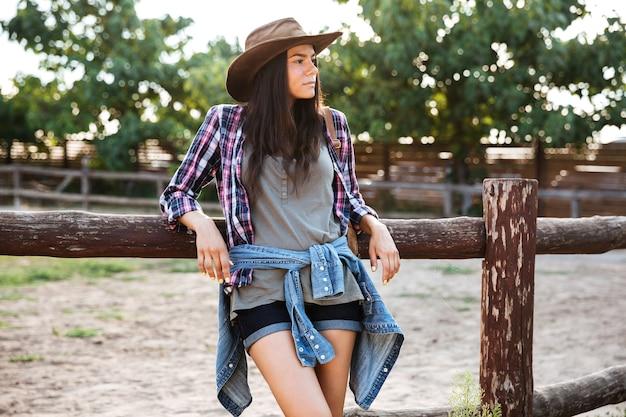 Entspanntes hübsches cowgirl der jungen frau mit hut, das auf ranch steht und ruht