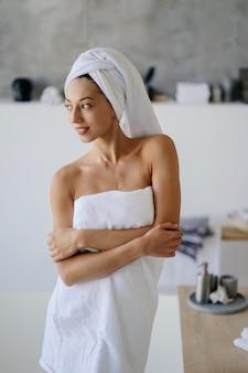 Entspanntes junges kaukasisches weibliches modell im weißen handtuch, fühlt sich nach dem duschen erfrischt, hat gesunde saubere weiche haut, posiert im gemütlichen badezimmer. frauen-, schönheits- und hygienekonzept.