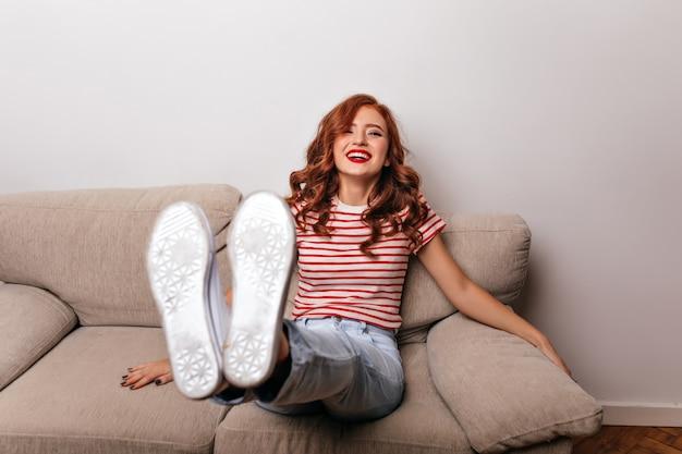 Entspanntes lustiges mädchen, das auf sofa mit lächeln sitzt. erfreute ingwerdame posiert auf der couch und lacht.