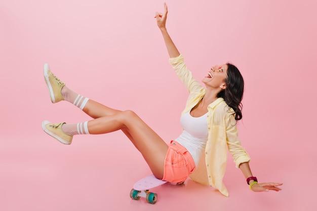 Entspanntes mädchen im hellen sommeroutfit, das auf skateboard mit den beinen oben und lachend sitzt. schöne junge brünette dame in den gelben schuhen, die zeit mit longboard verbringen.