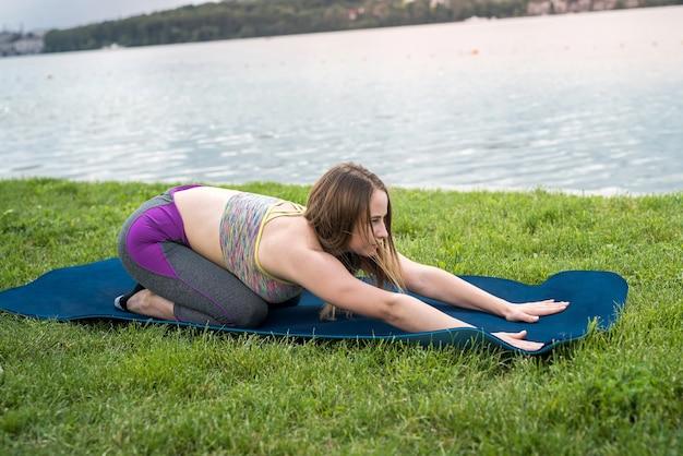 Entspanntes mädchen in sportbekleidung, das dehnen, meditationsübung, atemübung auf yogamatte nahe see tut
