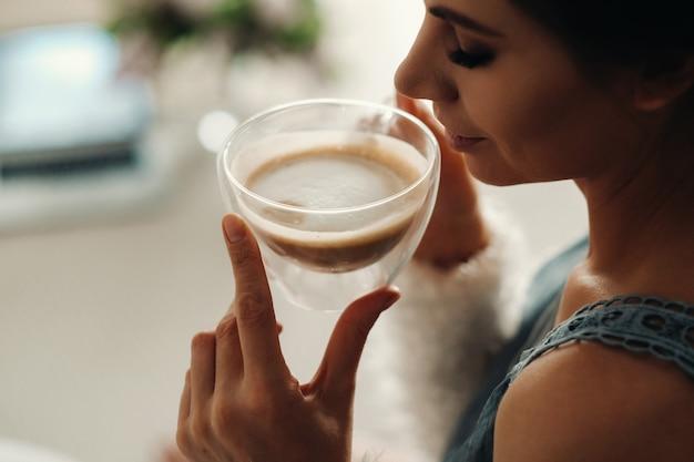 Entspanntes mädchen zu hause, das kaffee trinkt. innerer frieden. das mädchen sitzt bequem auf dem sofa und trinkt kaffee