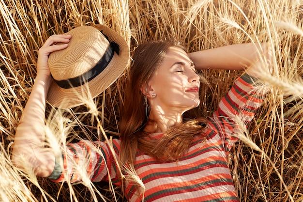 Entspanntes magnetmodell, das im weizenfeld liegt, zeit in der natur genießt, sich vor der sonne versteckt, ihren strohhut abnimmt, ihn in einer hand hält, zur seite schaut und in hochstimmung ist. naturkonzept.