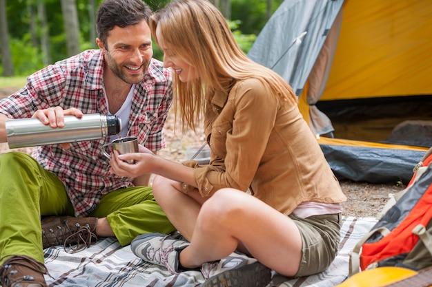 Entspanntes paar, das im wald genießt und kaffee trinkt