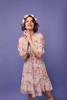 Entspanntes weibliches modell im frühlingskleid posiert. spektakuläre kaukasische dame mit rosen im haar suchen.