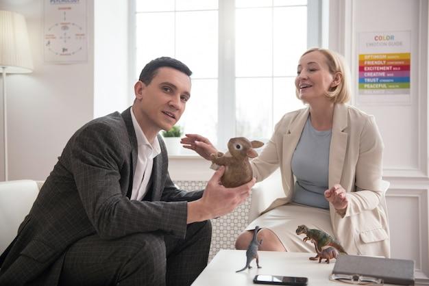 Entspannung. attraktiver positiver mann, der kamera betrachtet, während er mit reifem psychologen spricht