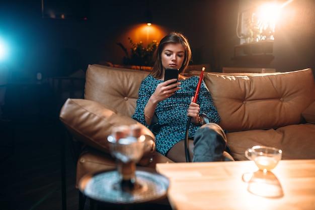 Entspannung der jungen frau, rauchende wasserpfeife an der bar. mädchen raucht shisha im nachtclub
