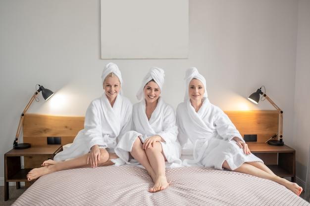 Entspannung. drei lächelnde erwachsene hübsche frauen in weißen bademänteln und handtüchern auf dem kopf, die barfuß auf dem bett im spa ruhen?