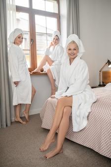 Entspannung. erwachsene lächelnde frau im weißen bademantel, die auf dem bett sitzt, eine freundin auf der fensterbank, die zweite in der nähe des fensters im ruheraum im spa steht?