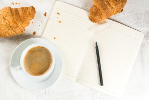 Entspannung. job. planung von angelegenheiten. weiße steintabelle mit einem notizbuch für anmerkungen, fälle, aufgaben. eine tasse duftenden frisch gebrühten kaffee. frisch gebackene croissants. bleistift. kopieren sie die draufsicht des raumes