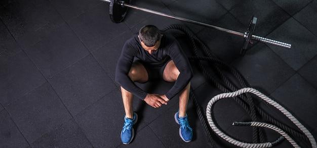 Entspannung nach dem training. blick von oben auf den bärtigen jungen mann, der beim sitzen auf der gymnastikmatte wegschaut
