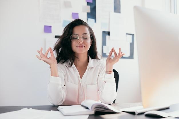 Entspannung und meditation junge frau am arbeitsplatz