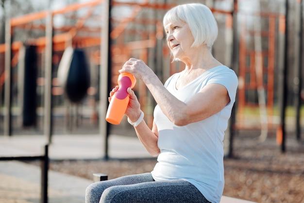 Entspannung. zufriedene blonde frau, die eine flasche saft hält und sich während des trainings entspannt