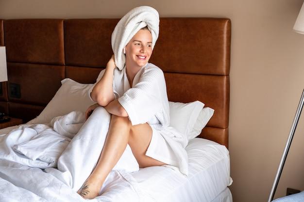 Entspannungsfrau im häuslichen stil mit bademantel und handtuch nach der dusche, morgens im luxushotel