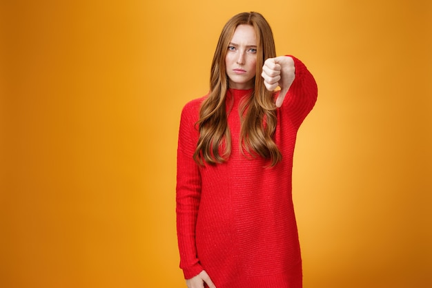 Enttäuscht verärgert und ernst aussehende attraktive rothaarige frau der 20er jahre in rotem strickkleid, die die stirn runzelt, mit abneigung schaut, mit dem daumen nach unten in abneigung und unzufriedenheit über die orangefarbene wand