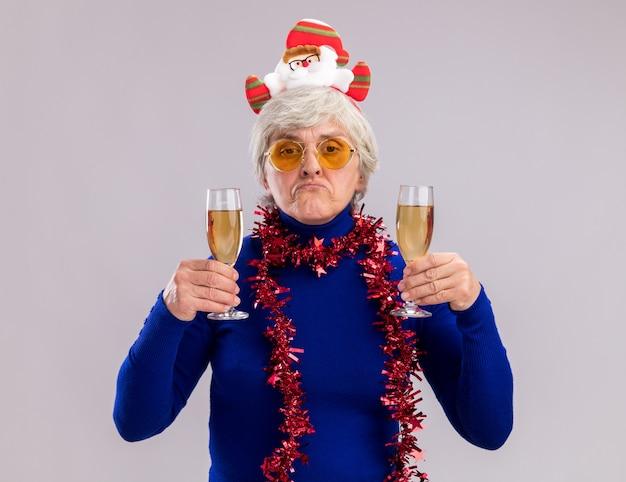 Enttäuschte ältere frau in sonnenbrille mit weihnachtsstirnband und girlande um den hals hält gläser champagner isoliert auf weißer wand mit kopierraum
