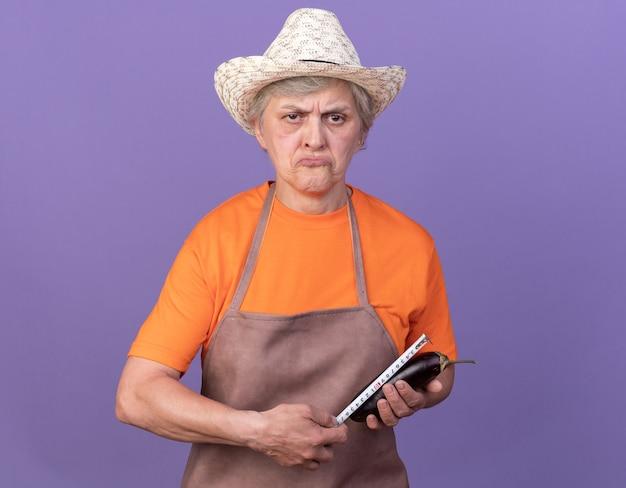 Enttäuschte ältere gärtnerin mit gartenhut, die auberginen mit maßband auf lila misst