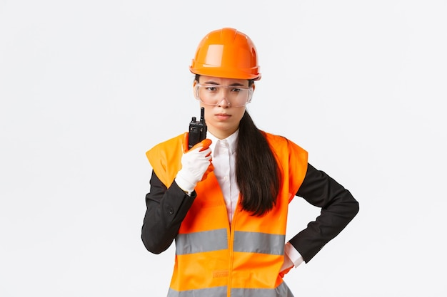 Enttäuschte asiatische bauingenieurin, technikerin oder industriemanagerin in sicherheitsuniform, die mitarbeiter über walkie-talkie anruft und personal über funkkommunikation im unternehmen ausschimpft