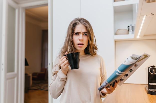 Enttäuschte braunhaarige dame im beigen hemd, das magazin liest