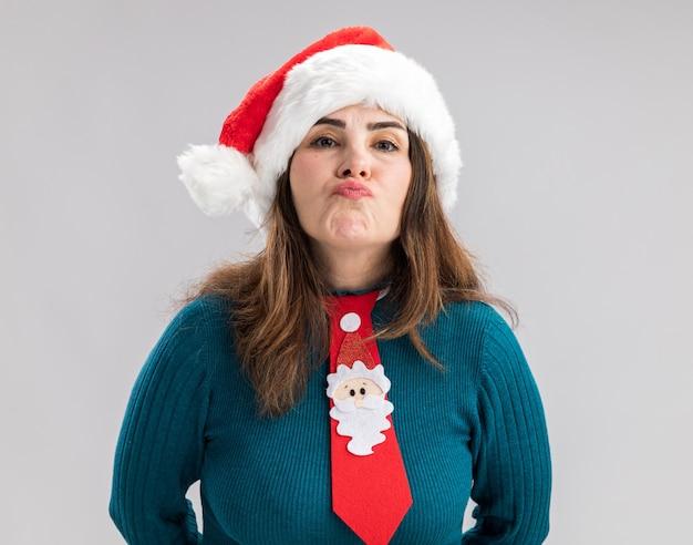 Enttäuschte erwachsene kaukasische frau mit weihnachtsmütze und weihnachtsmann-krawatte isoliert auf weißer wand mit kopierraum