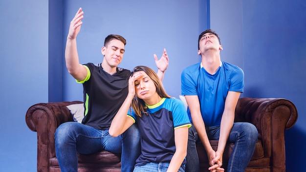 Enttäuschte fußballfans auf der couch