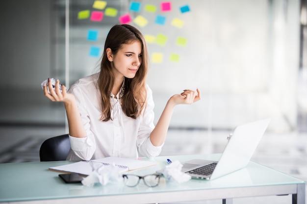 Enttäuschte geschäftsfrau, die in ihrem büro in weißen kleidern am laptop arbeitet