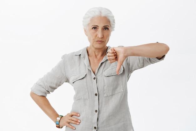 Enttäuschte großmutter zeigt daumen nach unten und verzieht verzogen das gesicht