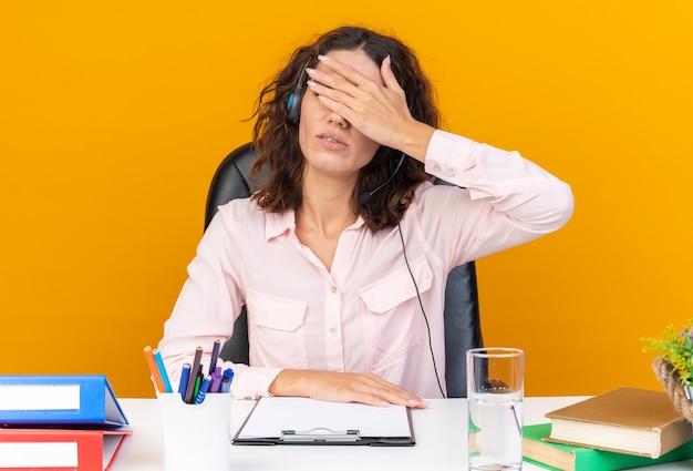 Enttäuschte hübsche kaukasische callcenter-betreiberin auf kopfhörern, die am schreibtisch mit bürowerkzeugen sitzen, die ihre augen mit der hand schließen