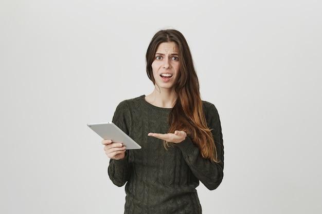 Enttäuschte junge attraktive frau, die sich über etwas im digitalen tablett beschwert